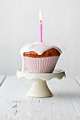 A muffin with dripping icing and a burning candle