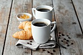 Mugs of coffee on a napkin with coffee beans served with a croissant and jam