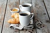 Kaffeebecher auf Serviette mit Kaffeebohnen, Croissant und Marmelade