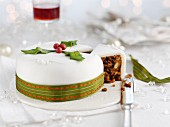 A white Christmas cake with a green ribbon