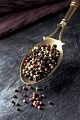 Coloured peppercorns on a measuring spoon
