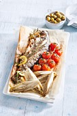 Fried fish with chicory and cherry tomatoes on baking paper