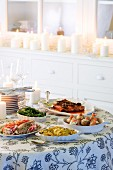 A Christmas buffet with various dishes and atmospheric candles