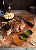 A rack of beef ribs with chimichurri sauce and chips
