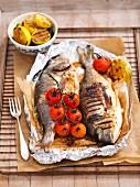 Gegrillte Fische mit Tomaten und Zitronen auf Alufolie am Grillgitter