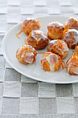Profiteroles with icing sugar and orange zest