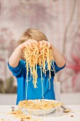 A boy holding spaghetti in his hands