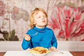 A little boy eating spaghetti with a fork