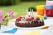 A birthday cake on a garden table