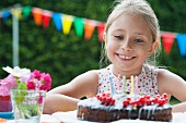 A girl sitting in front of a birthday cake