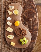 A cheese board with bread and grapes (seen from above)