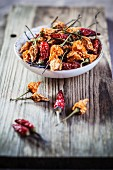 Various different dried chilli peppers on a wooden board and in a bowl