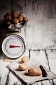 Kartoffeln auf Schneidebrett und alter Küchenwaage