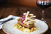Lamb on a bed of chickpeas with fried aubergine sticks