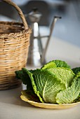 A savoy cabbage next to a straw basket and an olive oil jug