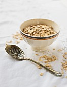 A bowl of porridge oats and a vintage spoon