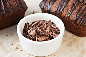 Grated chocolate in a bowl in front of chocolate cake