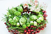 A Christmas wreath made of Brussels sprouts, cranberries and rosemary with a ribbon