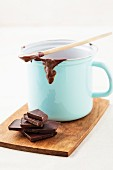 Chocolate and a cup with pudding on the rim