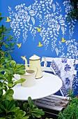 Wandbild mit Kolibris und Wysteria auf einer blau bemalten Gartenmauer, davor ein weißer Tisch und Stuhl mit Kaffeekanne