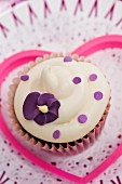 A cupcake decorated with a purple sugar flower on a paper doily