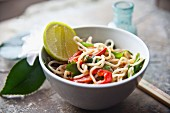 Fried noodles with vegetables, chilli peppers, five spice powder and limes (Asia)
