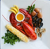 Lobster and mussels with corn on the cob, butter sauce, potatoes and lemons