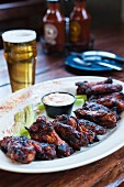 Grilled chicken wings with celery, dip and a glass of beer