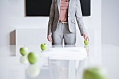 Apples rolling around on a conference table with a businesswoman in the background
