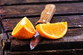 Two orange wedges with a knife on a wooden crate
