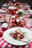 Weihnachtstisch mit rot-weiss kariertem Tischtuch, Kerzen, Stoffservietten und Marmeladengläsern