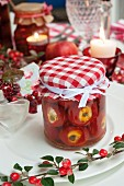 A jar of stuffed peppers with cream cheese on a table laid for Christmas