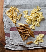 Various different pasta shapes on a tea towel