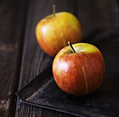 Two apples on a black baking tray
