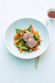 Pork fillet on a bed of colourful vegetables