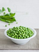 A bowl of fresh peas with pea pods in the background