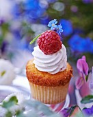 A cupcake topped with cream and decorated with a raspberry