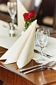Gedeckter Platz am Tisch mit Serviette, Glas und Besteck in einem Restaurant