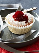 A cupcake topped with cranberry jam and icing sugar