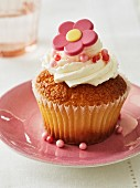 A cupcake decorated with buttercream and a sugar flower