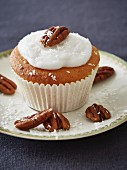 A coconut cupcake decorated with pecan nuts