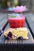 A slice of berry cake and a strawberry drink on a wooden table