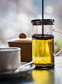 Green jasmine tea in a cup and in a tea press