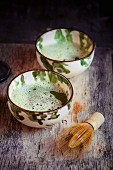Bowls of matcha tea with a bamboo whisk