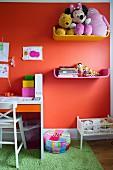 Farbige Ablagen mit Kuscheltieren und Büchern an orangeroter Wand, seitlich Schreibtisch im Kinderzimmer