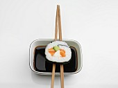 A maki sushi roll with salmon and cucumber balanced on chopsticks over a dish of soy sauce