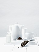 An arrangement of coffee beans, ground coffee and coffee crockery