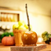 A caramel apple with a stick in front of apples and pumpkins in a kitchen