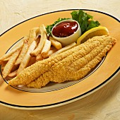 Catfish with a cornflour coating served with fries, lemon and ketchup
