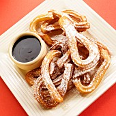 Churros (deep fried dough with icing sugar, Mexico) with chocolate sauce